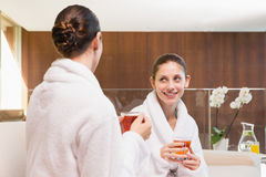 Smiling women in bathrobes having tea Royalty Free Stock Photography