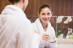 Smiling women in bathrobes having tea. Two smiling young women in bathrobes having tea Stock Photography