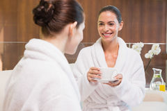 Smiling women in bathrobes having tea. Two smiling young women in bathrobes having tea Royalty Free Stock Image