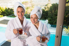 Smiling women in bathrobes having tea. Two smiling young women in bathrobes having tea outdoors Stock Image