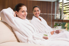 Smiling women in bathrobes sitting on couch Stock Photos