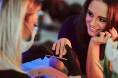 Smiling woman has a manicure from manicurist. royalty free stock photos