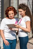 Smiling women with breast cancer awareness ribbons using digital. Tablet stock image