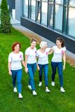Smiling women with breast cancer awareness ribbons walking together on green. Lawn stock photos