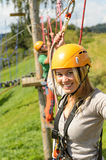 Woman with helmet smiling in adventure park. Smiling women climbing on high wire in adventure park Stock Images