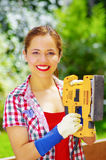 Smiling women with colorfull clothes holding a eletric sander Stock Images