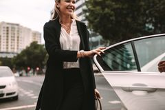 Smiling woman commuter getting out of a taxi. Smiling women commuter getting out of a taxi. Businesswoman getting off a cab stock image
