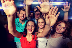 Smiling women dancing in club. Party, holidays, celebration, friends and people concept - smiling friends dancing and waving hands in club Stock Photography