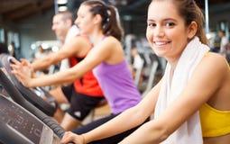 Indoor biking. Smiling women doing indoor biking in a fitness club Royalty Free Stock Image