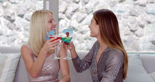 Smiling women drinking cocktail. On the sofa stock video