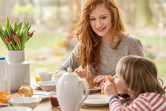 Woman eating croissants with son. Smiling women eating croissants with her son at a table with tulips stock photos