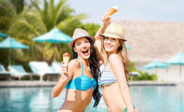 Smiling women eating ice cream over swimming pool Stock Photography