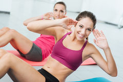 Smiling women exercising at the gym. Smiling women exercising at gym on a mat and looking at camera, fitness and workout concept Royalty Free Stock Images