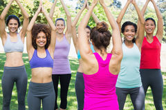 Smiling women exercising with instructor at park. Portrait of smiling women exercising with instructor at park Royalty Free Stock Photos
