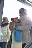 Smiling women with gifts and shopping bags by window during winter Stock Photo
