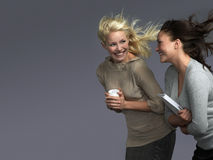 Smiling Women With Hair Blowing In Wind. Two smiling young businesswomen with hair blowing in wind against gray background stock images