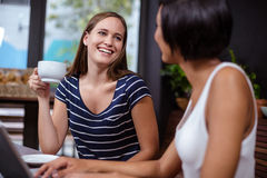 Smiling women having coffee together Stock Images