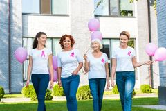 Smiling women holding pink balloons and walking together breast cancer awareness. Concept stock images