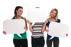 3 smiling women holding  speech bubbles, one  covering her face Stock Photo