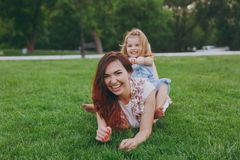 Smiling woman in light dress and little cute child baby girl lie on green grass in park rest play and have fun. Mother. Smiling women in light dress and little stock images