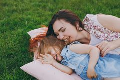 Smiling woman in light dress and little cute child baby girl lie on green grass in park rest, play and have fun. Mother. Smiling women in light dress and little royalty free stock images