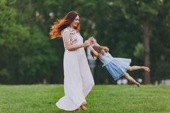 Smiling woman in light dress and little cute child baby girl playing circling around on green grass lawn in park. Mother. Smiling women in light dress and little stock photos