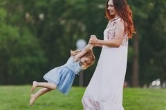 Smiling woman in light dress and little cute child baby girl playing circling around on green grass lawn in park. Mother. Smiling women in light dress and little royalty free stock images