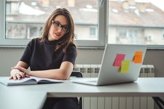 Smiling woman looking at laptop screen at the office. Smiling women looking at laptop screen at the office while ready to write into her notebook royalty free stock image