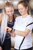 Smiling women looks at training statistics on smart sports clock. Two young smiling women having a break looking at the wearable health monitoring sports clock royalty free stock photography