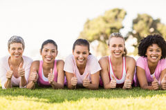 Smiling women lying in a row and wearing pink for breast cancer Royalty Free Stock Image
