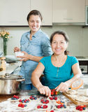 Smiling women making  pies with berries Royalty Free Stock Image