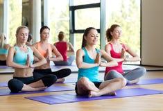Smiling women meditating on mat in gym Royalty Free Stock Photos