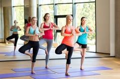 Smiling women meditating on mat in gym Royalty Free Stock Photo
