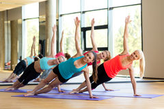 Smiling women meditating on mat in gym Stock Images