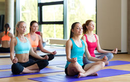 Smiling women meditating on mat in gym Stock Photography