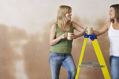 Smiling Women With Mugs By Step Ladder Royalty Free Stock Photos