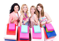 Smiling women with multicolor shopping bags. Portrait of beautiful smiling women with multicolor shopping bags standing on a white background stock photo