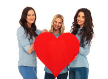 3 smiling women offering their big red heart to you Stock Image
