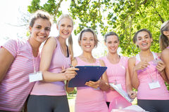 Smiling women organising event for breast cancer awareness. On a sunny day royalty free stock photo