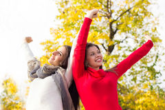 Smiling women with outstretched arms. Young women standing,arms are spread open wide and her head is tilted back Royalty Free Stock Images
