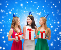 Smiling women in party caps with gift boxes Royalty Free Stock Photo