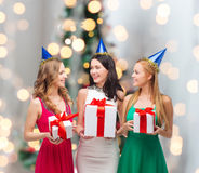Smiling women in party caps with gift boxes Stock Image
