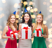 Smiling women in party caps with gift boxes Royalty Free Stock Image