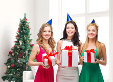 Smiling women in party caps with gift boxes Royalty Free Stock Images