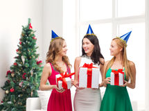 Smiling women in party caps with gift boxes Stock Photography