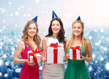 Smiling women in party caps with gift boxes Stock Images