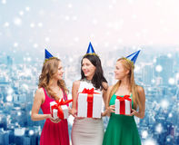 Smiling women in party caps with gift boxes Royalty Free Stock Photography