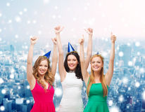 Smiling women in party caps showing thumbs up Royalty Free Stock Photography