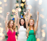 Smiling women in party caps showing thumbs up Royalty Free Stock Images