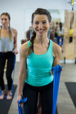 Smiling women performing stretching exercise with resistance band Royalty Free Stock Photos